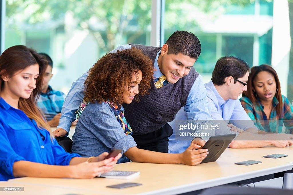 Diverse college freshman in class with Hispanic professor : Stock Photo