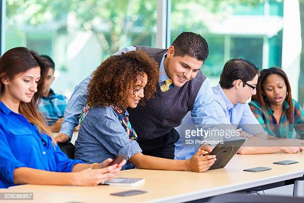 Diverse college freshman in class with Hispanic professor