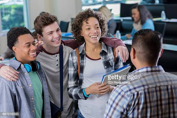 Diverse college friends meet with professor before class