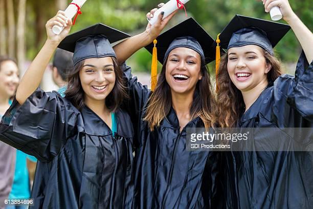 Diverse college grads celebrate after receiving diplomas