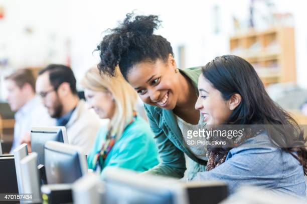Diverse college students using computers in library or computer lab