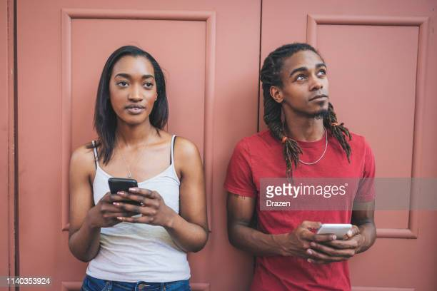 diverse community in usa - couple using phone - afro caribbean ethnicity stock pictures, royalty-free photos & images