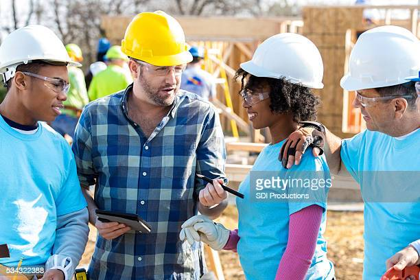 Diverse construction crew discusses project