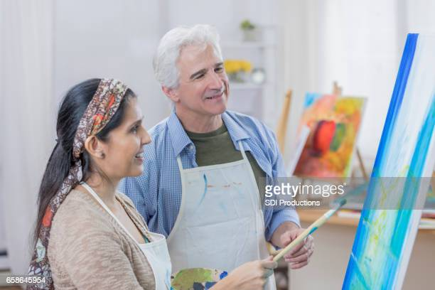 Diverse couple paint together in art studio