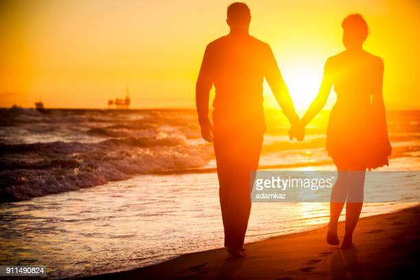diverse couple walking on beach at sunset - honeymoon stock pictures, royalty-free photos & images