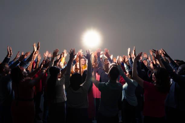 Diverse crowd with arms raised around bright light