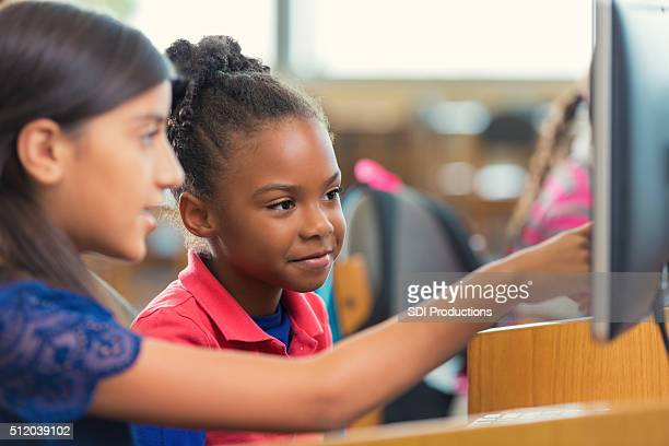 Diverse elementary school girls using computer during class