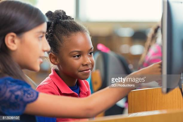Grande escola primária meninas com computador durante a aula