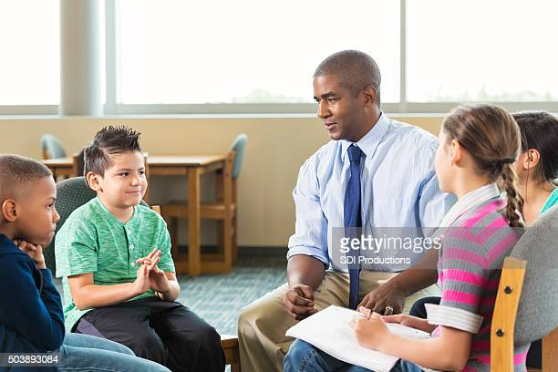 Diverse elementary students meeting with counselor after school