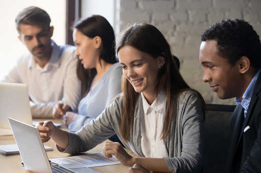 Diverse employees work together cooperating in office 1129819911