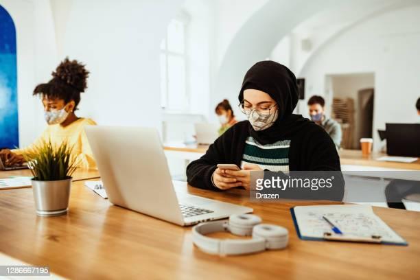 divers entrepreneurs avec des masques de visage dans le bureau - hijab feet photos et images de collection