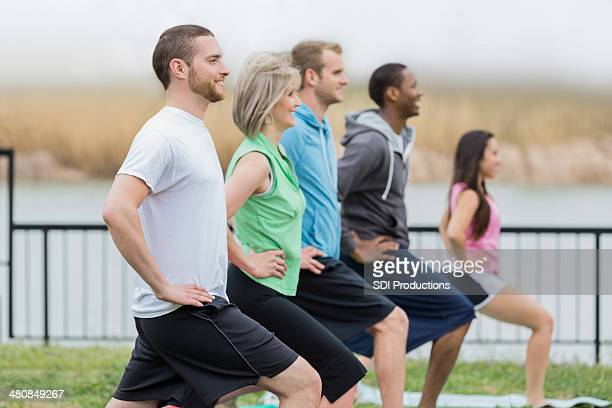 Diverse exercise club stretching during outdoor yoga class