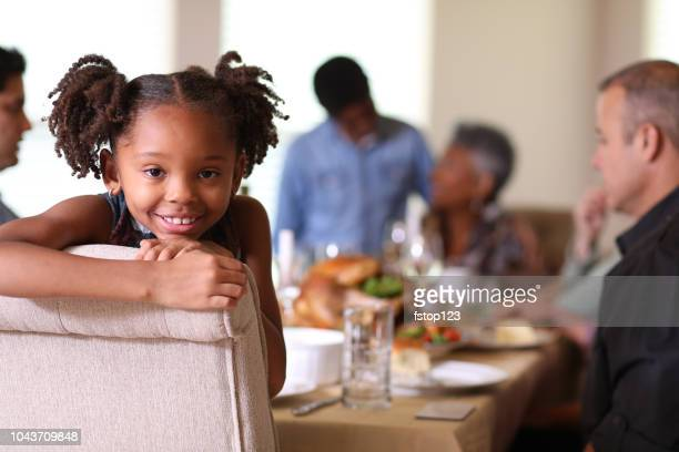 Diverse family at dining table eating Thanksgiving dinner.