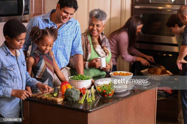 diverse family in home kitchen cooking thanksgiving dinner. - kids thanksgiving stock pictures, royalty-free photos & images