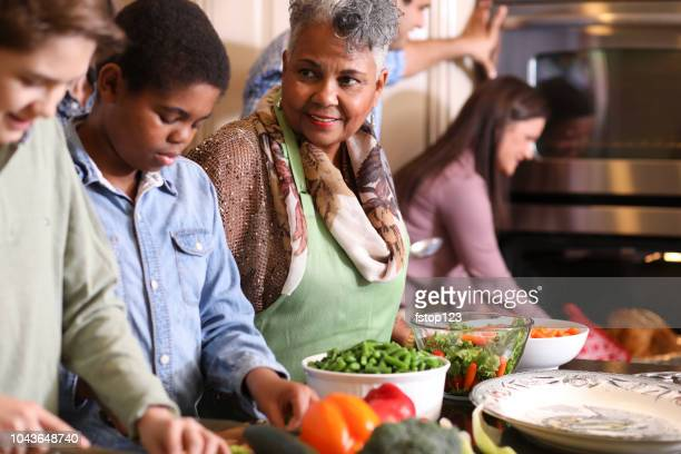 diverse family in home kitchen cooking thanksgiving dinner. - black family dinner stock photos and pictures