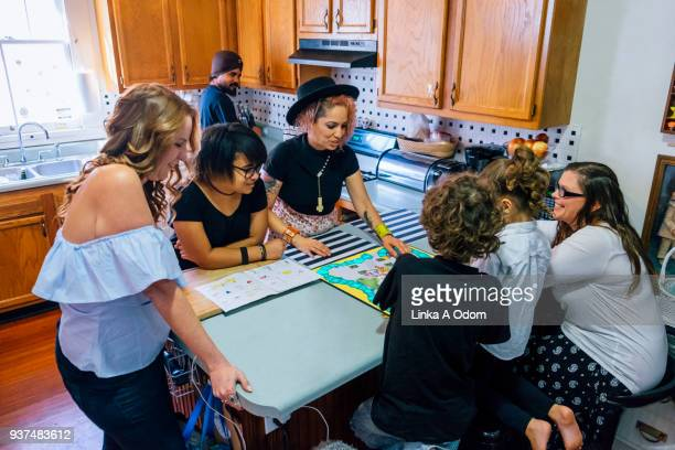 Diverse Family Playing Board Game in Kitchen
