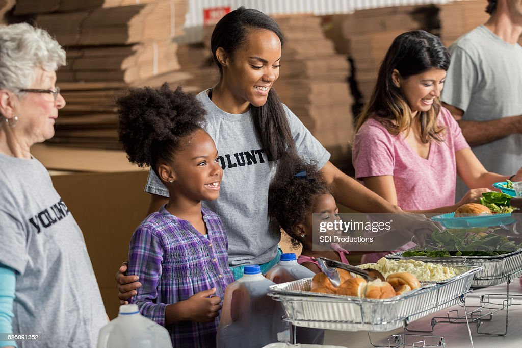 Diverse family volunteers together in soup kitchen : Stock Photo