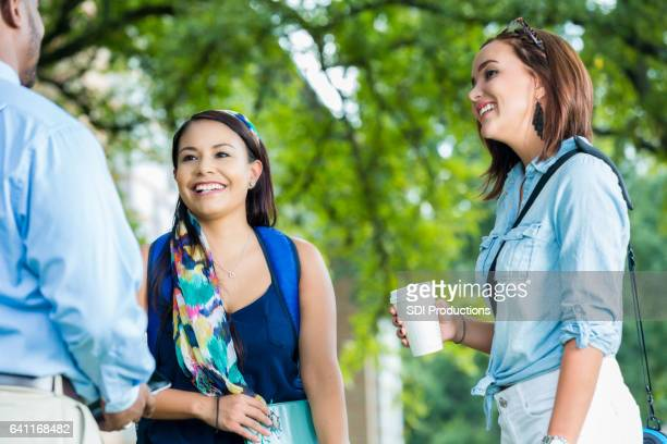 Diverse female college students talk with professor