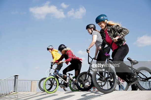 diverse female cyclists at starting line on bmx race track - olympisch park sportlocatie stockfoto's en -beelden