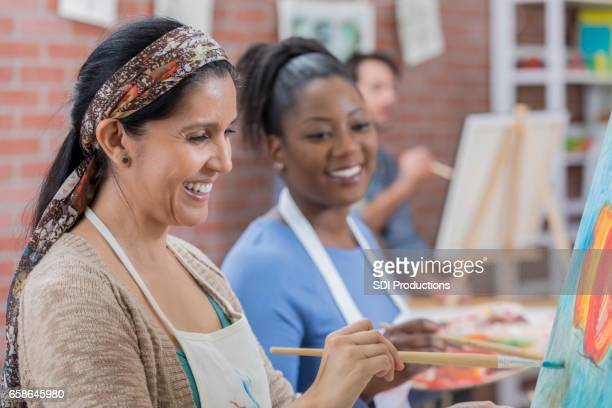Diverse female friends paint together during art class
