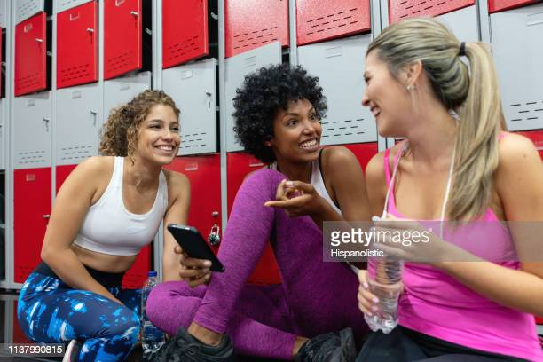 diverse freundinnen entspannen sich nach dem training im fitnessstudio und im umkleideraum im gespräch und lächeln - umkleideraum stock-fotos und bilder