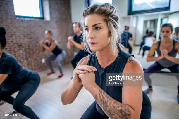 diverse fitness class doing squats - 30 39 years stock pictures, royalty-free photos & images