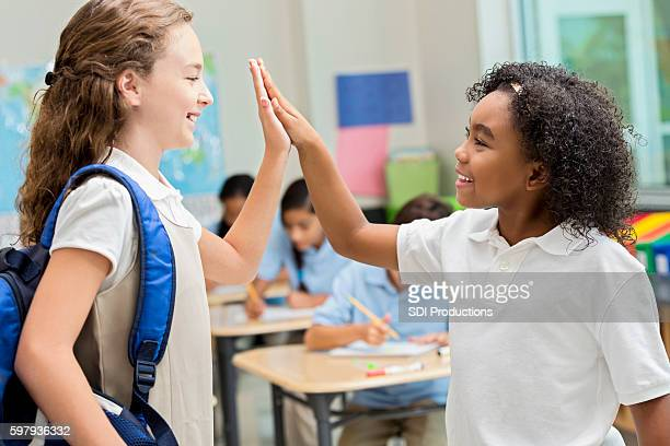 Diverse friends high five during class