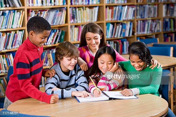 Diverse friends studying together in school library