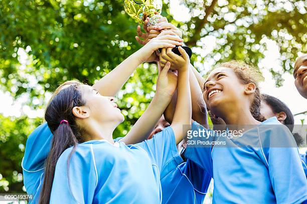 Diverse girls' soccer team holding up a trophy