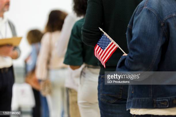 diverse group in line to vote; one holds american flag - election voting stock pictures, royalty-free photos & images