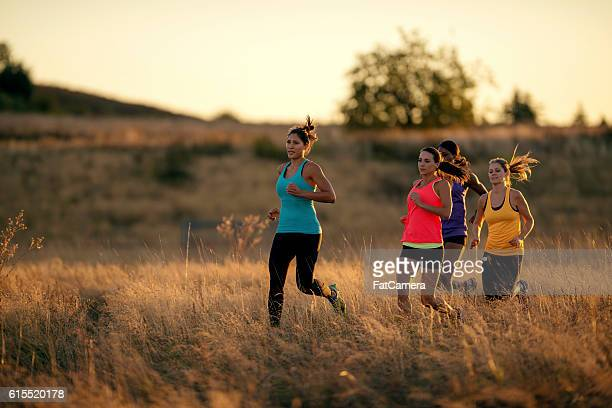 Diverse group of adult females trail running in tall grass