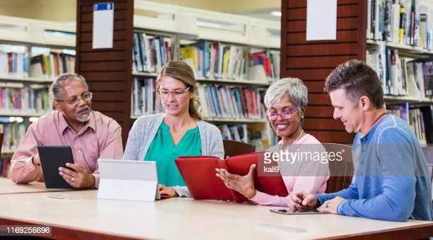 mångsidig grupp av vuxna studenter i biblioteket, e-läsare - group e bildbanksfoton och bilder