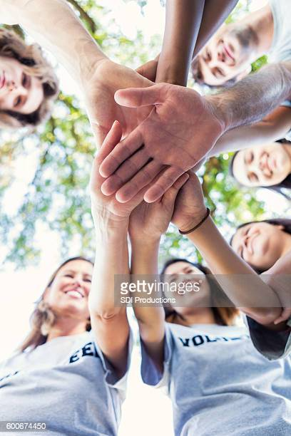 diverse group of adults outdoors in a huddle - vertical stock pictures, royalty-free photos & images