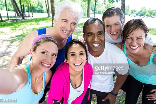 Diverse group of athletes posing for team photo after exercising