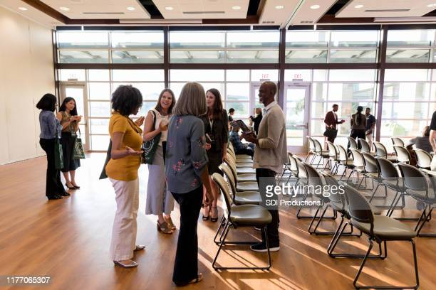 diverse group of attendees chat during conference break time - town hall meeting stock pictures, royalty-free photos & images