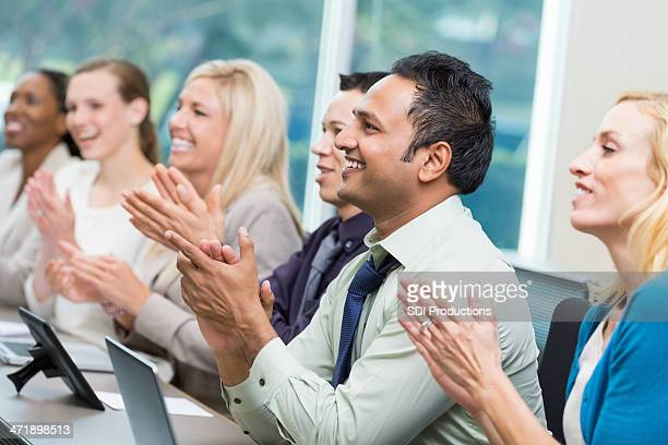 Diverse group of business executives applauding during conference
