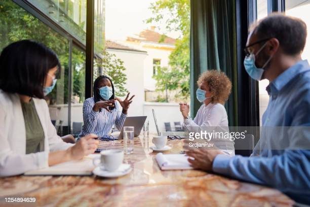 diverse group of business people having a meeting at the coffee shop while wearing protective masks during coronavirus pandemic - internet cafe stock pictures, royalty-free photos & images