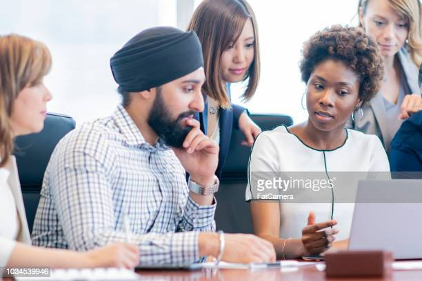 diverse group of businesspeople meets at a conference table - sikh stock pictures, royalty-free photos & images