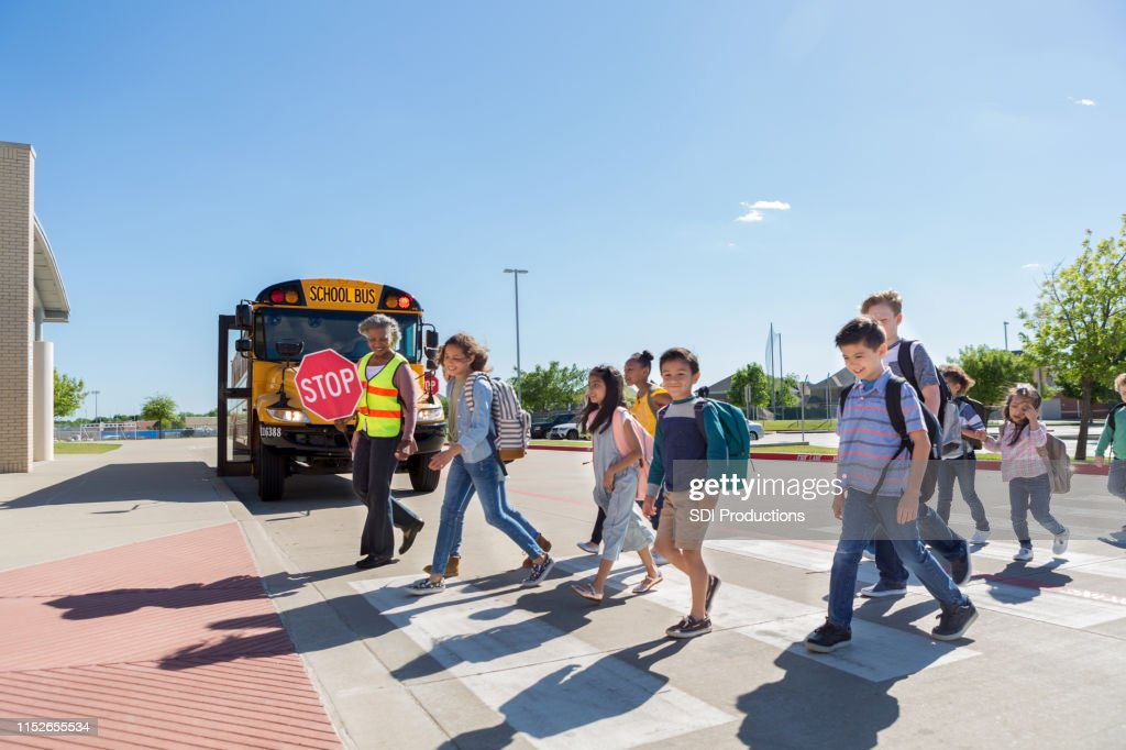 Diverse group of children cross safely to school : Stock Photo