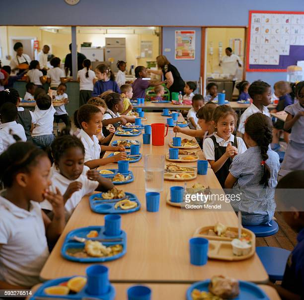 A diverse group of children eat their school dinner and chat at Kingsmead Primary School The school primarily serves children who live on the...