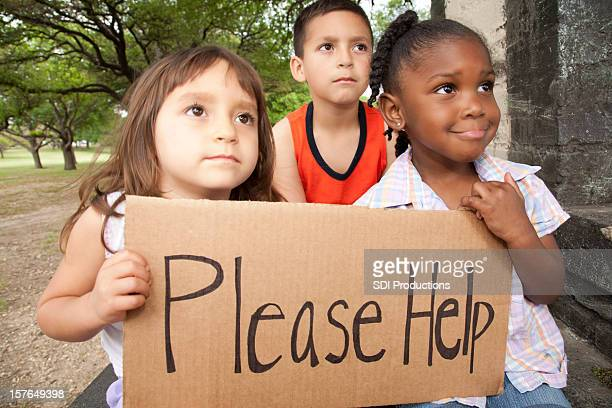 Diverse Group of Children Holding a Please Help Sign