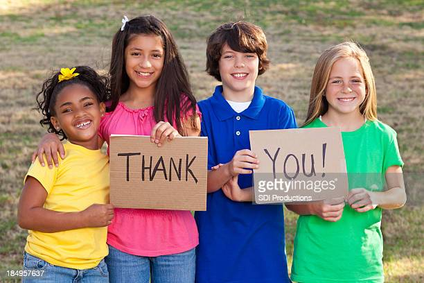 diverse group of children holding thank you signs - thank you stock pictures, royalty-free photos & images