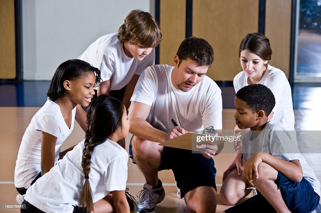 Diverse group of children in gym with coach : Stock Photo
