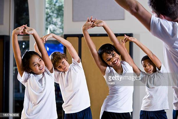Diverse group of children in gym with physical education teacher