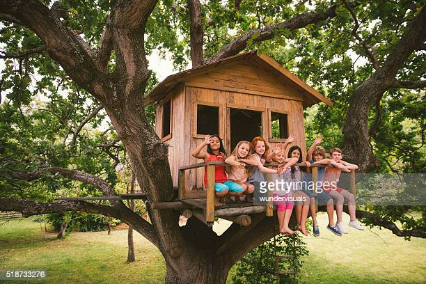 diverse group of children smiling and waving in a treehouse - Treehouse