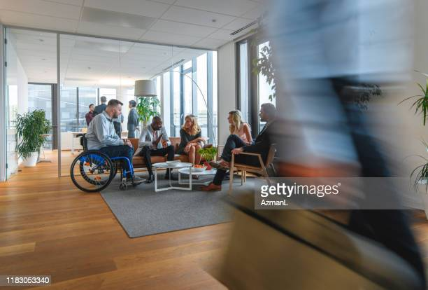 diverse group of colleagues conversing in busy office lobby - persons with disabilities stock pictures, royalty-free photos & images