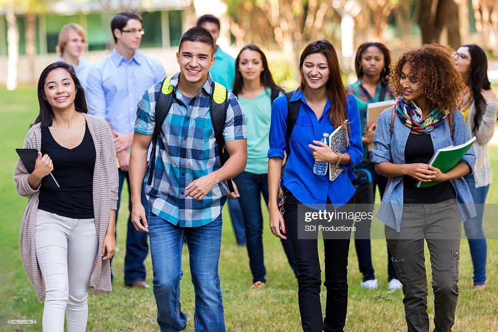 Diverse group of college students walking on beautiful campus : Stock Photo