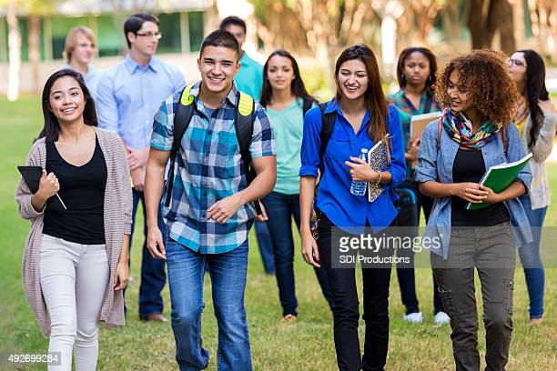 Diverse group of college students walking on beautiful campus