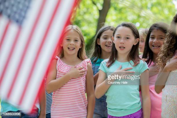 Diverse group of elementary school age girls saying Pledge of Allegiance to the American flag outdoors