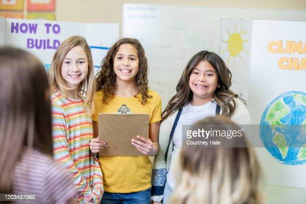diverse group of elementary school girls presenting their group science fair entry - exhibition stock pictures, royalty-free photos & images
